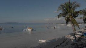 Bohol Philippines aerial shot. Ocean, waves, coastline, sun, ships, boats, palm trees, sand, beach, island, drone video.