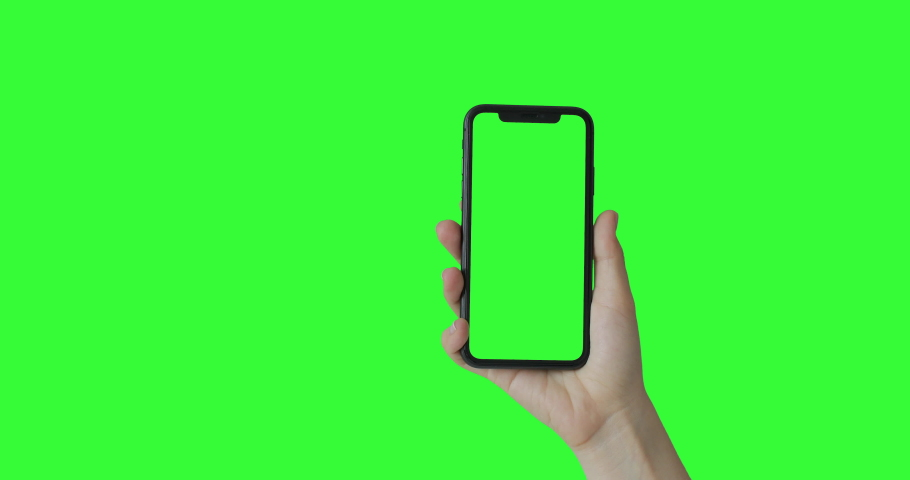 Woman hand holding the smartphone on green screen chroma key background.  Mobile phone mock-up for your product. The iPhone Xr model in vertical orientation portrait mode. 2020 - USA, California