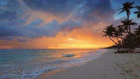 Dramatic sea sunrise over tropical island beach with exotic coconut palm trees