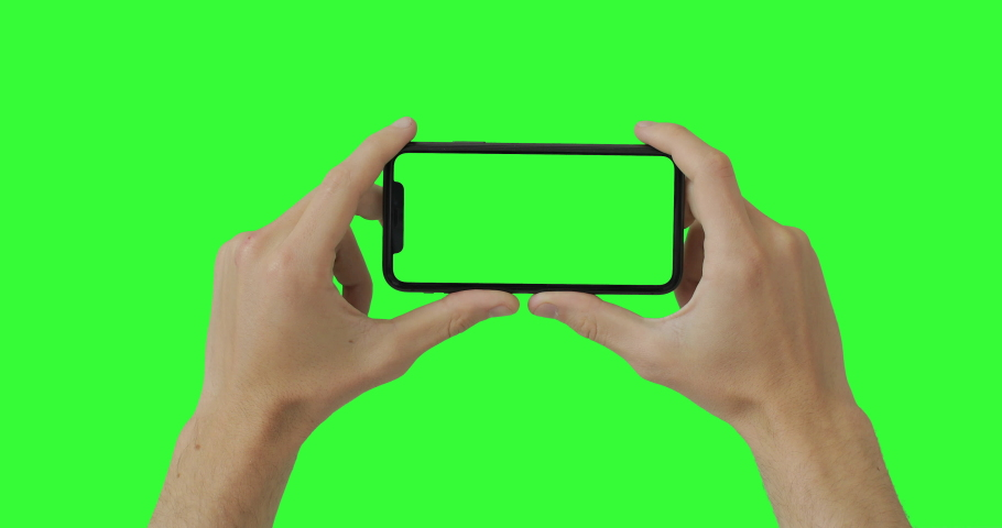 Male man hands holding the smartphone on green screen chroma key background. Mobile phone mock-up for your product. The iPhone 11 model in horizontal orientation landscape mode. 2020 - USA, NY