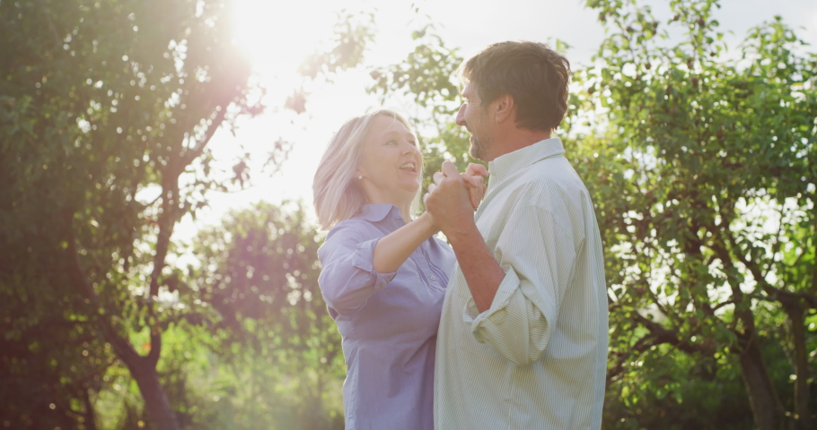 Authentic shot of lovely happy mature couple is enjoying time together and having fun dancing to celebrate their timeless love on a background of a green nature. Concept: love, family, marriage, dance