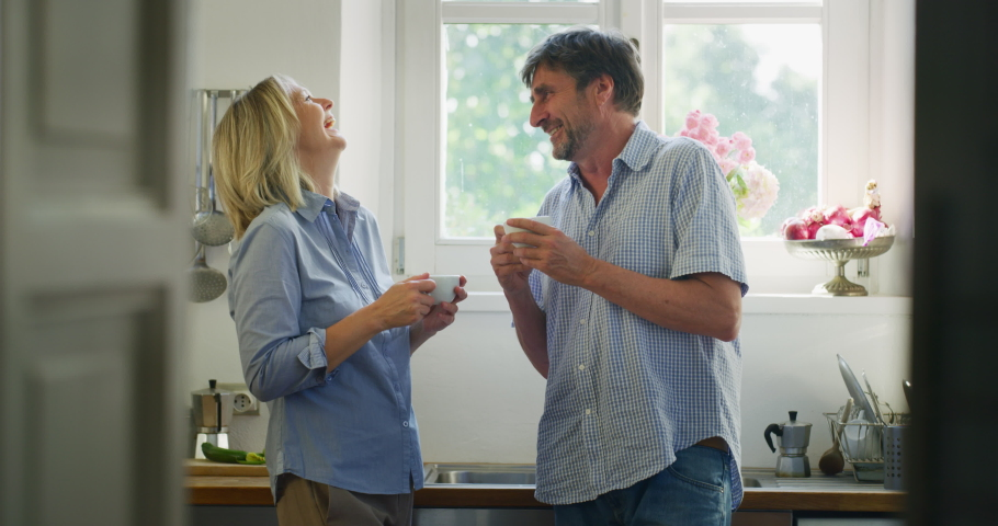 Authentic shot of lovely happy mature couple is enjoying  to have a breakfast together in a kitchen just wake up in a morning at home. Concept: love, family, marriage, happiness and freedom