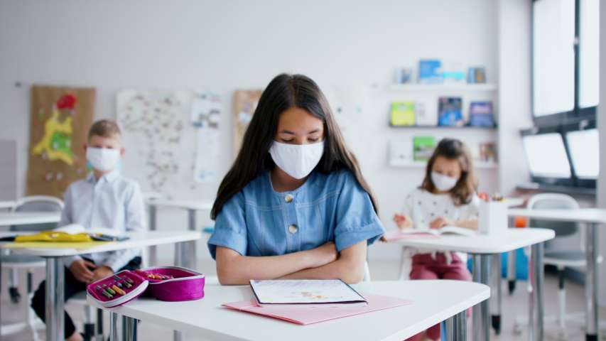 Child with face mask back at school after covid-19 quarantine and lockdown. | Shutterstock HD Video #1053578888