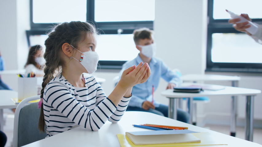 Teacher, children with face mask at school after lockdown, disinfecting hands. Royalty-Free Stock Footage #1053578906