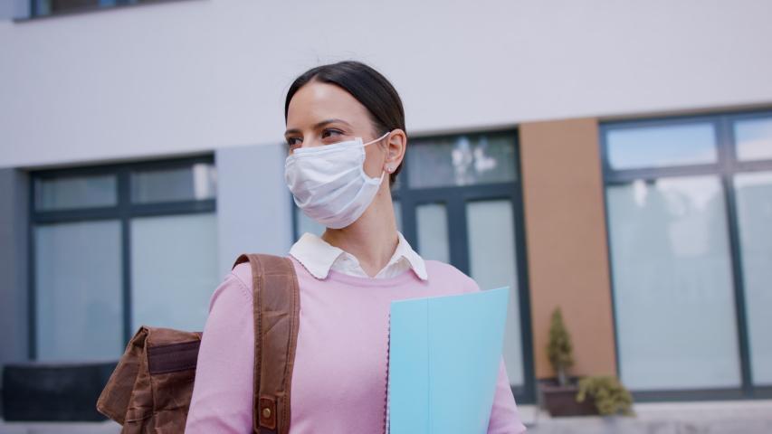 Portrait of happy teacher in front of school building, taking off face mask.   Shutterstock HD Video #1053579116
