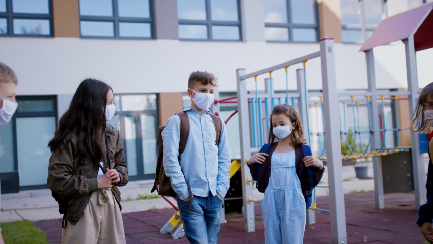 Children with face mask going back to school after covid-19 lockdown, greeting. | Shutterstock HD Video #1053579122