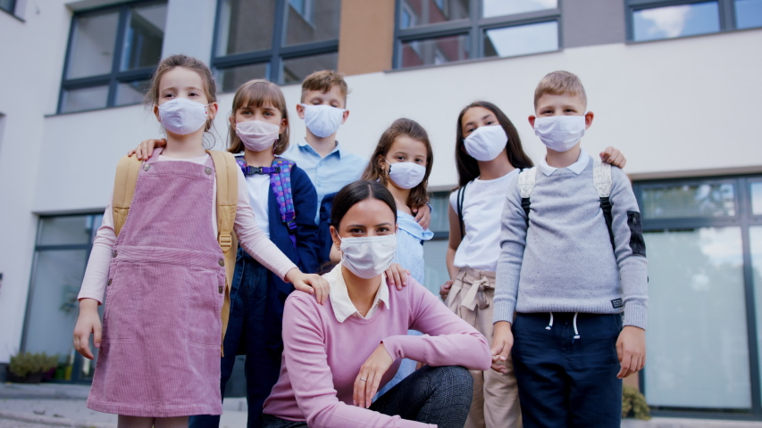 Group of children, teacher with face masks outdoors at school after covid-19 lockdown. | Shutterstock HD Video #1053579134