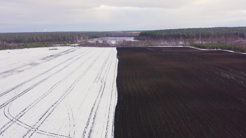 Dolly zoom. A blue tractor plows a field covered with snow. Behind the tractor is black earth. Russia, Ural, Aerial View, Departure of the camera