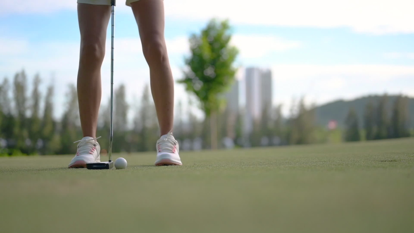 Woman golf player in action of putting a golf ball on the green run through a hole successfully