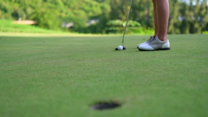 Woman golf player in action of putting a golf ball on the green run through a hole successfully Royalty-Free Stock Footage #1053585968