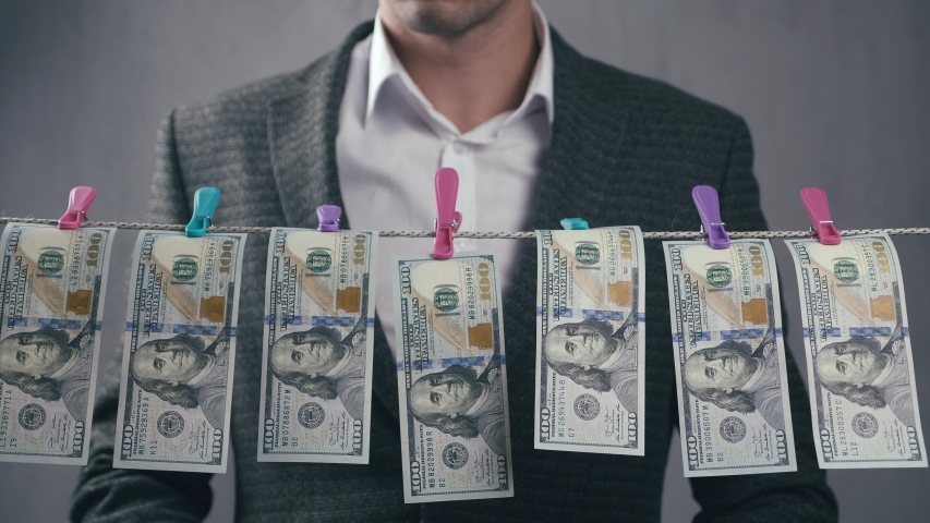 Male criminal launders money. A man dries dollar bills on a rope. Economic crime concept. | Shutterstock HD Video #1053587642