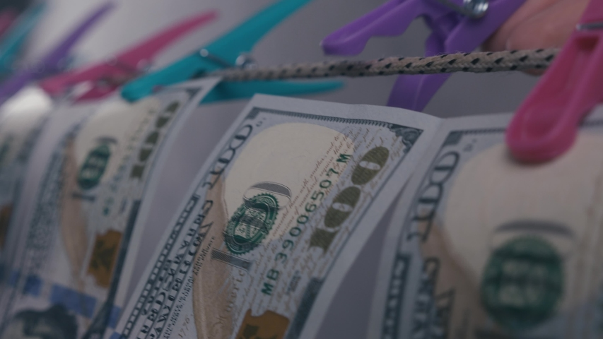 Money laundering concept. Dollar bills are dried on a rope. Pure money. | Shutterstock HD Video #1053587648