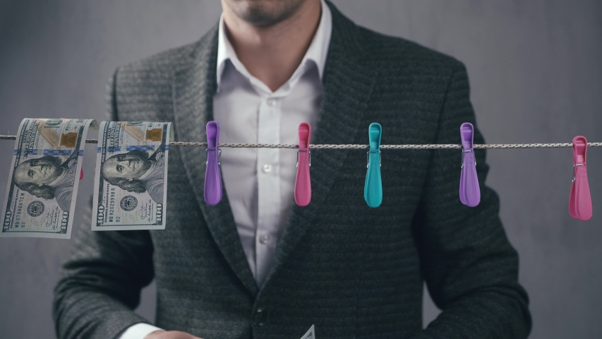 Male criminal launders money. A man dries dollar bills on a rope. Economic crime concept. | Shutterstock HD Video #1053587651