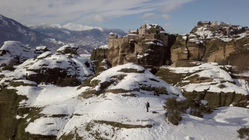 Aerial drone footage semi orbital flight over a photographer standing next to his tripod & camera at a lookout point near the Great Monastery and Varlam Monastery at Meteora in Greece in the winter | Shutterstock HD Video #1053588986
