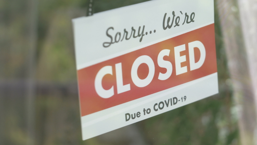 Closed sign hanging on the glass during pandemic time in 4K Slow motion 60fps | Shutterstock HD Video #1053590375
