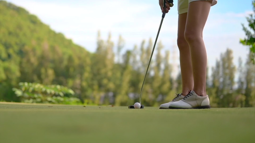Woman golf player in action of putting a golf ball on the green run through a hole in failure shot
