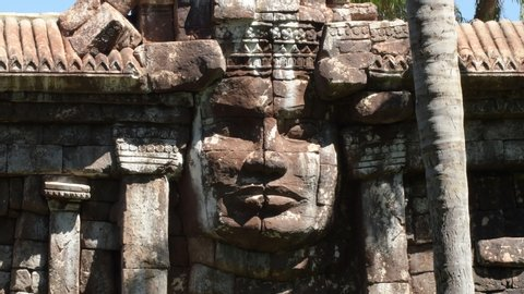 Ancient face of a god or goddess sculpted in stone in a Hindu or buddhist temple