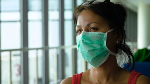 Portrait of a woman with dark hair at airport during wearing glasses and a face mask against Coronavirus Covid19, looking at camera