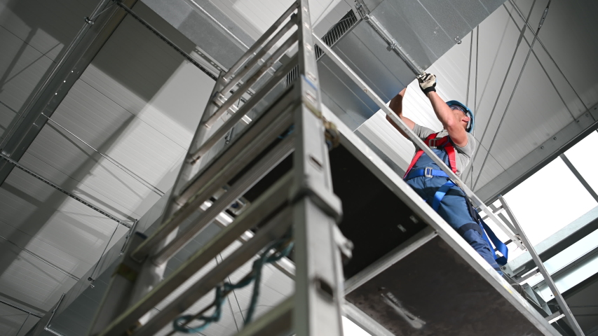 Air Duct Specialist Installing New Vent Shaft System On Ceiling Of Industrial Building. Royalty-Free Stock Footage #1053597254