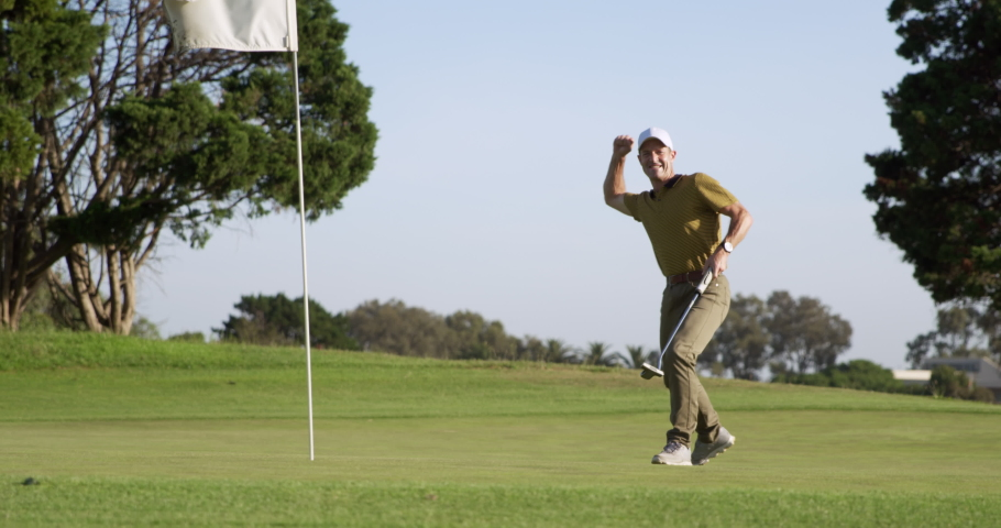 A Caucasian male golfer on a golf course on a sunny day wearing a cap and golf clothes, holding a golf club and putting the ball into the final hole, marked with a flagstick in the foreground