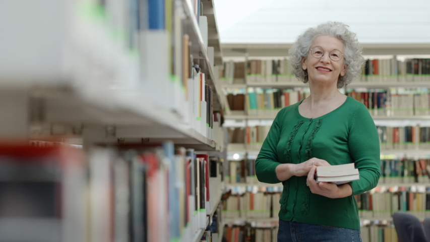 Portrait of happy senior retired woman choosing book in public library and taking it from shelf. Elderly lady reading books for pleasure, old people as reader for hobby smiling and looking at camera