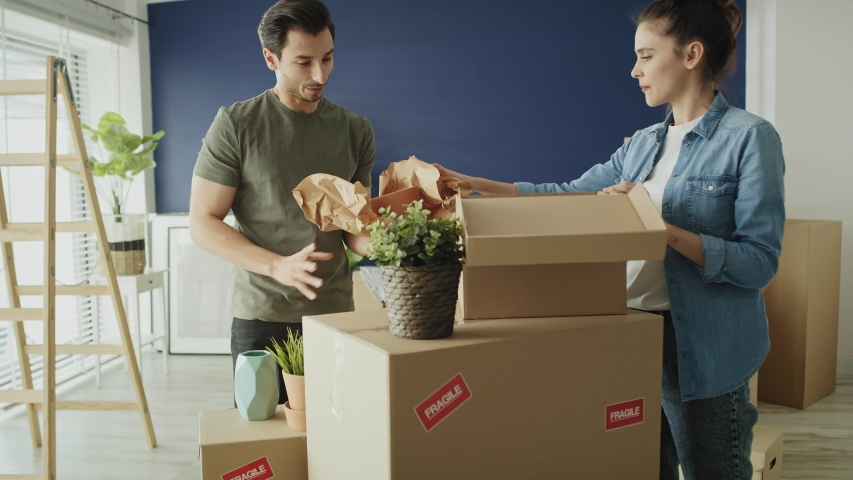 Video of couple packing things to boxes while moving house. Shot with RED helium camera in 8K Royalty-Free Stock Footage #1053617282