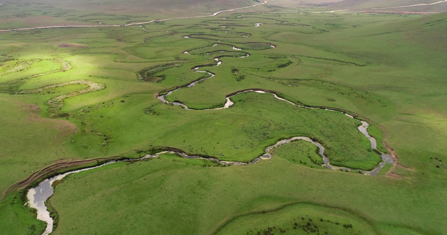 Meandering stream with mountains and clouds at The Persembe Plateau at Ordu, Turkey Drone and Aerial view. Nature, natural places. Village life.