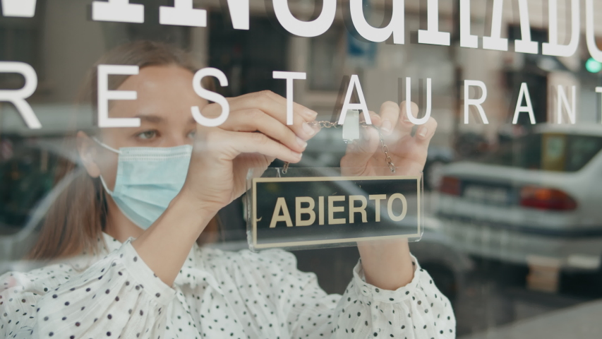 cafe or restaurants and business reopen after coronavirus quarantine is over. woman with face mask turning a sign from closed to open on a door shop. small business after post covid lockdown. Spain Royalty-Free Stock Footage #1053618533