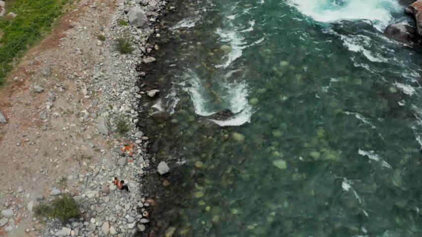 Drone revealing a foot bridge across wild blue river, in Astore Valley, Pakistan