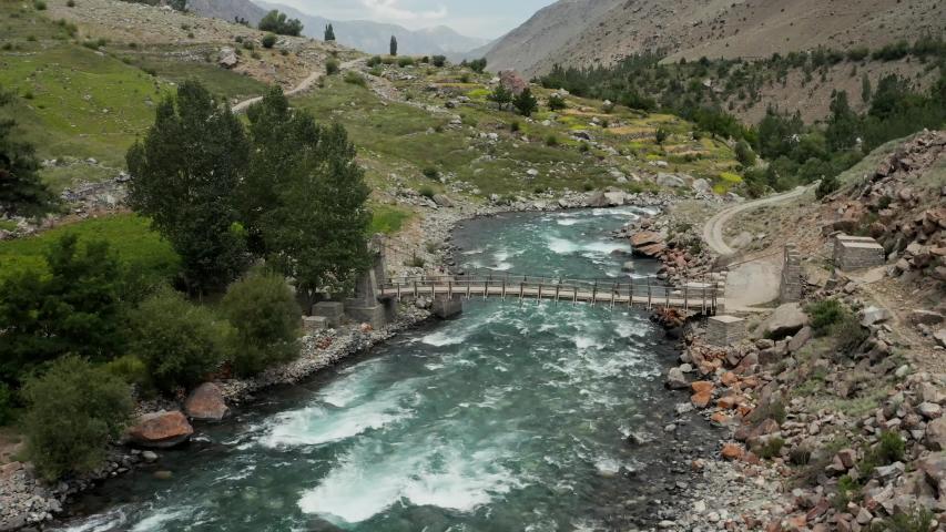 Drone flyover a foot bridge across wild blue river, in Astore Valley, Pakistan