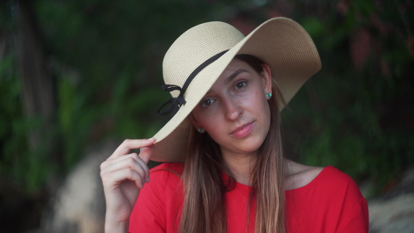 Portrait of attractive woman in hat looking into camera 4K. Girl in red dress peeps out the hat and smiles into the camera.