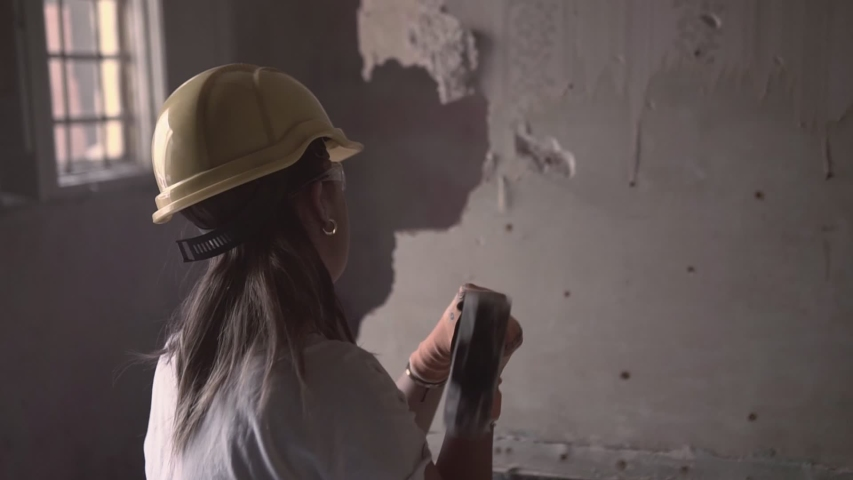 Back view video of a young construction worker woman wearing protective personal equipment trying and failing to break a wall with a big hammer and getting frustrated | Shutterstock HD Video #1053622175