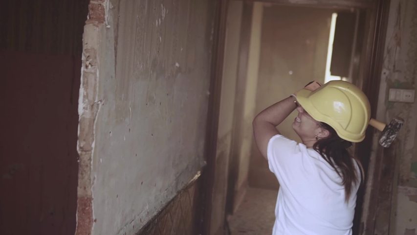 Slow motion video of a young construction worker womanhitting a wall with a hammer very hard and failing to break it wearing protective personal gear | Shutterstock HD Video #1053622181