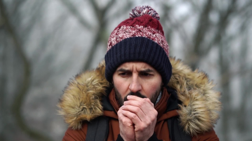 Bearded Caucasian male standing in forest and warming up his hands while looking to the side during cold winter day, SLOW MOTION. | Shutterstock HD Video #1053623396