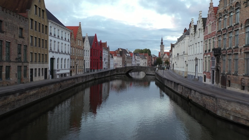 Low aerial fly over Bruges canals with a rise over a historic arch bridge. Quiet streets in the morning with commuters using public transport and architecture reflections in the water. | Shutterstock HD Video #1053624959