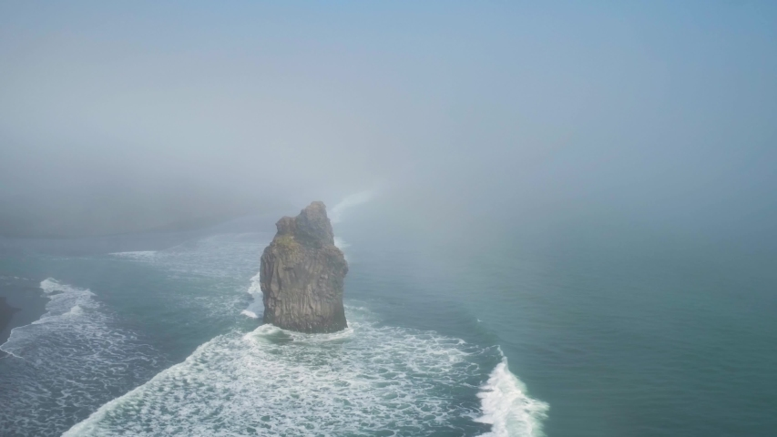 Reynisfjara coastal cliff sea stack, Iceland, aerial reveal through cloud haze | Shutterstock HD Video #1053624974