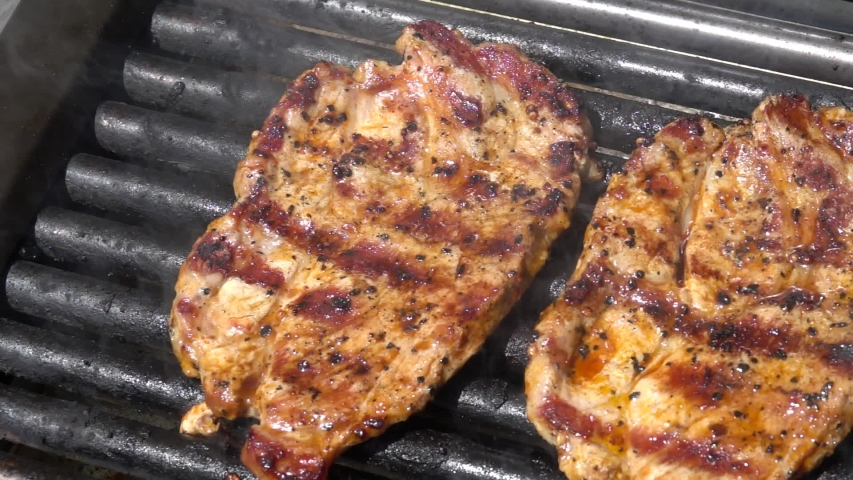 Grilling pork steaks. Delicious juicy meat steaks cooking on the grill. Slow motion 240 fps | Shutterstock HD Video #1053627092