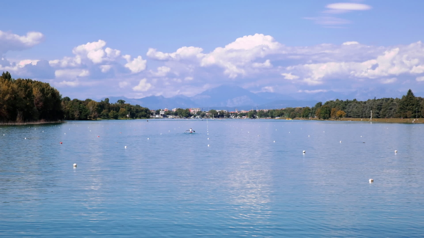 Time lapse of Idroscalo, an artificial lake in Milan, Italy. Old seaplane airport now a recreational and sports facility for kayak, canoe, rowing, sailing, swimming, horseback riding and water skiing Royalty-Free Stock Footage #1053628502
