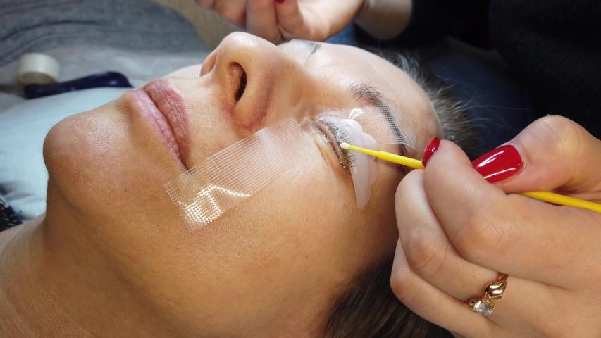 Beauty treatment. Beautician procedure of laminating eyelashes. Fixing of eyelashes. Closeup face.   Shutterstock HD Video #1053631250