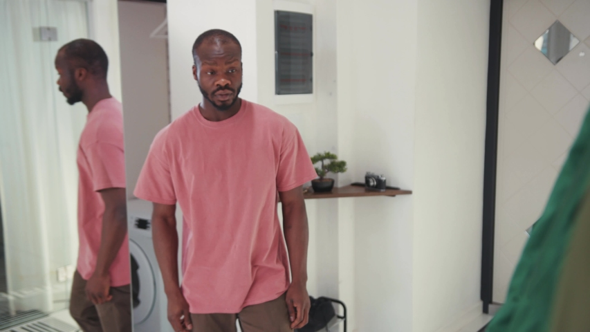 Young african american man puts on green jacket in front of mirror. Stylish guy getting dressed for work leaves the house going out. Casual people. Lifestyle. Apartment.