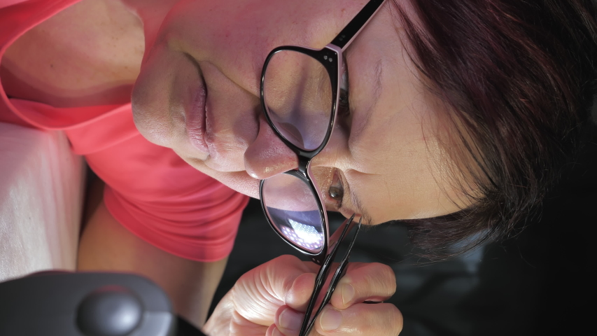 Vantaa.Finland-April 24.2020: A mature adult woman wearing her eyeglasses while plucking her hair on the eyebrows using the tweezers.Vertical Screen Orientation Video 9:16   Shutterstock HD Video #1053637085