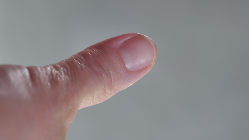 Cutinng of nails of the thumb of the mature adult lady using a small scissors.Vertical Screen Orientation Video 9:16   Shutterstock HD Video #1053637220