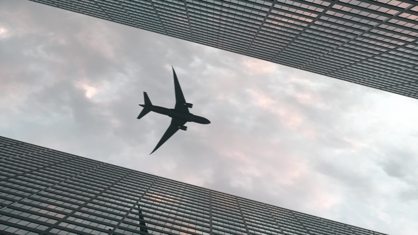Airplane flies over office skyscrapers against a beautiful sky | Shutterstock HD Video #1053639545