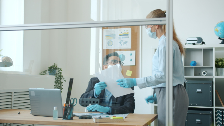 Slow motion of business people wearing face masks and gloves working in office cooperating during covid-19 global epidemic. Man is using modern laptop typing. Royalty-Free Stock Footage #1053639791