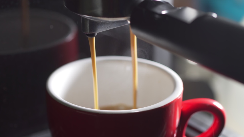 Footage B Roll of Pouring coffee stream from machine in cup. Home making hot Espresso. Using filter holder. Flowing fresh ground coffee. Drinking roasted black coffee in the morning.  Royalty-Free Stock Footage #1053640061