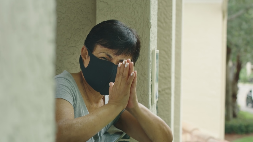 Elderly woman with protective face mask putting hands in prayer position Royalty-Free Stock Footage #1053642668