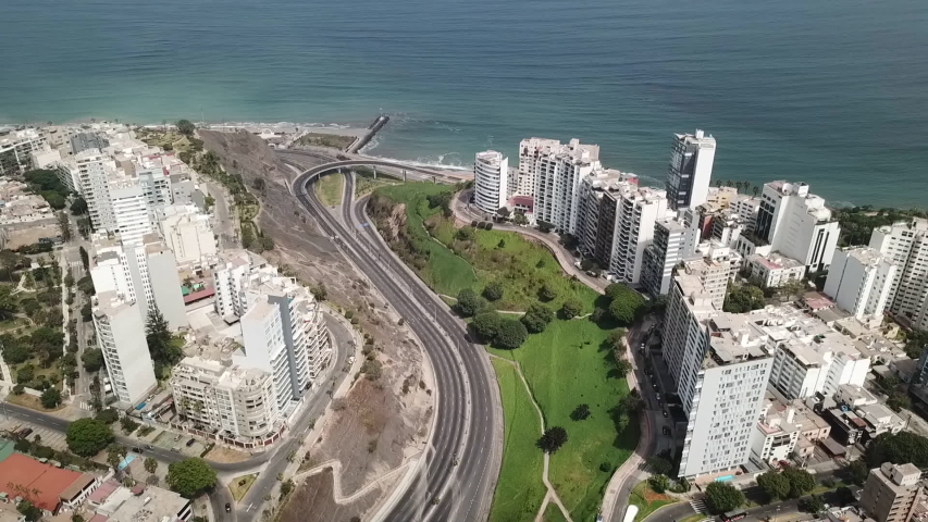 Aerial view of Lima city during coronavirus lockdown in Peru 2020. Flight over Miraflores and Pacific ocean coast. Empty roads and streets, no transport. Self-isolation and quarantine due to pandemic Royalty-Free Stock Footage #1053643799