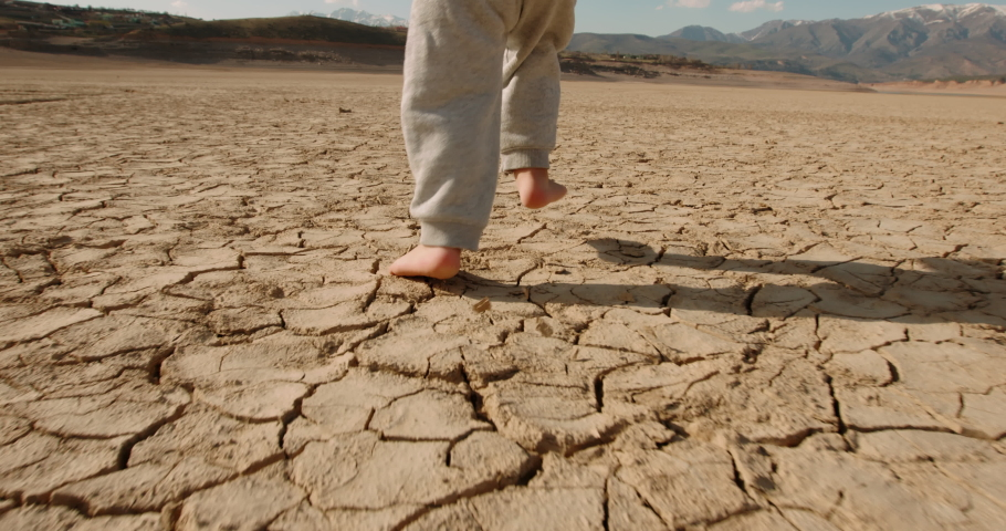 Close up shot of legs of baby boy running on cracked soil, destroyed by overuse, climate change and flood - ecological issues, save our planet 4k footage Royalty-Free Stock Footage #1053645425
