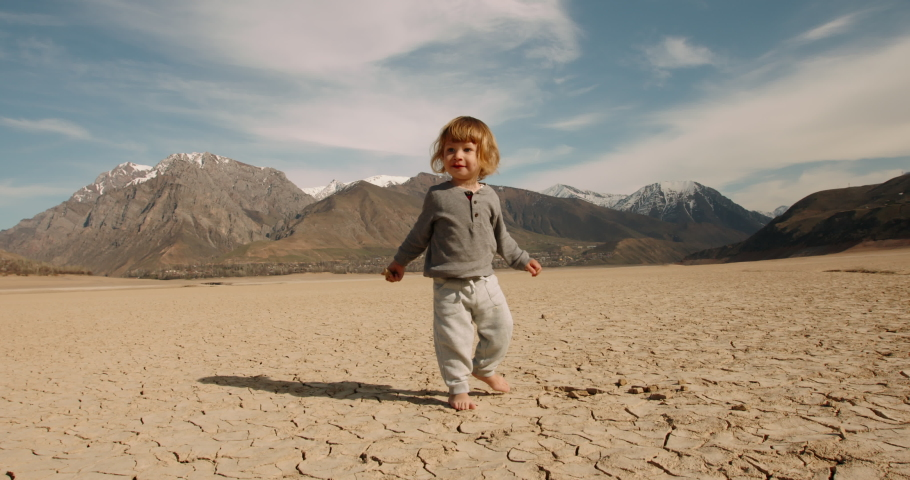Funny caucasian baby boy running on deserted ground. Cracked soil land after erosions and desertification - ecology, save our planet concept 4k footage Royalty-Free Stock Footage #1053645428