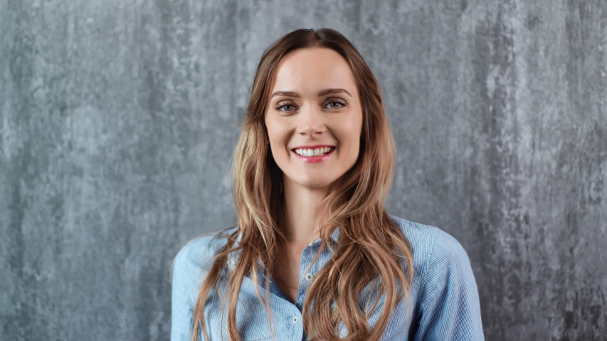 Portrait of joyful casual blonde woman smiling with open mouth isolated on gray studio background. Pretty female with natural beauty laughing having fun. Medium close up shot on 4k RED camera   Shutterstock HD Video #1053654260